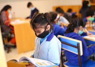 Dzieci w maseczkach uczące się w szkole